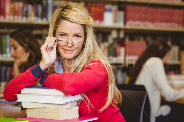 Student with reading glasses leaning on a stack of books Stock photo © wavebreak_media