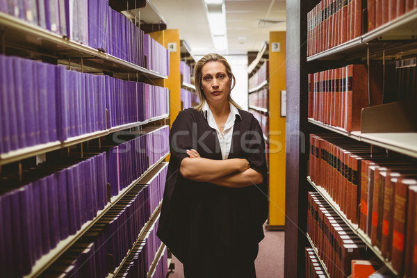 Unsmiling lawyer standing between shelfs with arms crossed Stock photo © wavebreak_media