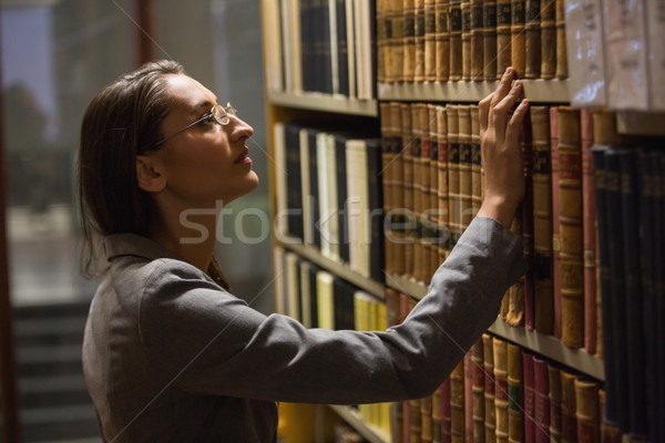Lawyer picking book in the law library Stock photo © wavebreak_media