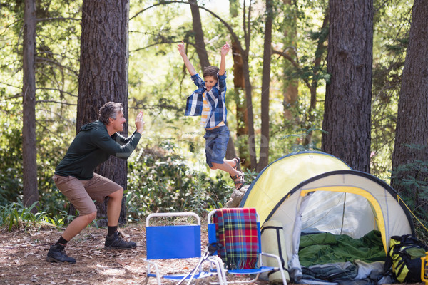 Father photographing playful boy jumping at campsite Stock photo © wavebreak_media