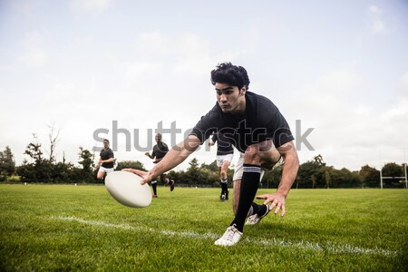 Rugby player holding ball while kneeling on grass Stock photo © wavebreak_media