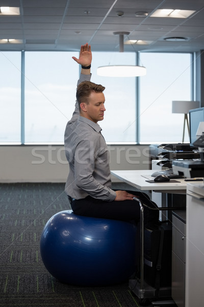 Executive performing stretching exercise on fitness ball Stock photo © wavebreak_media