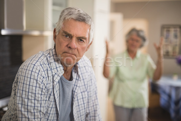 Portrait of unsmiling senior man with angry woman in background Stock photo © wavebreak_media