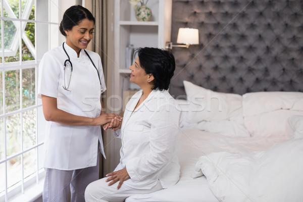 Sorridente enfermeira reconfortante feminino paciente cama Foto stock © wavebreak_media