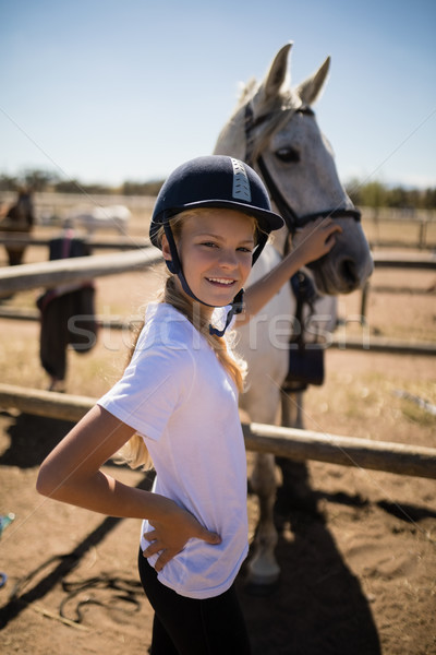 Smiling girl touching the horse in the ranch Stock photo © wavebreak_media