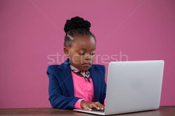 Serious businesswoman using laptop at desk Stock photo © wavebreak_media