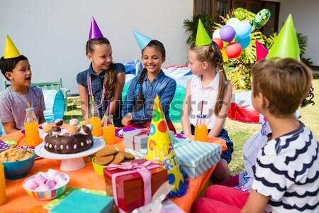 Children looking at girl holding gift Stock photo © wavebreak_media