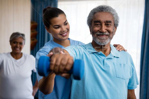 Nurse guiding senior man in exercising Stock photo © wavebreak_media