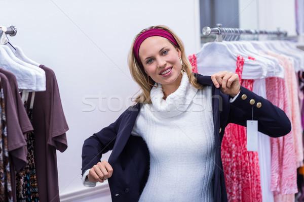 Smiling woman putting on blue coat Stock photo © wavebreak_media