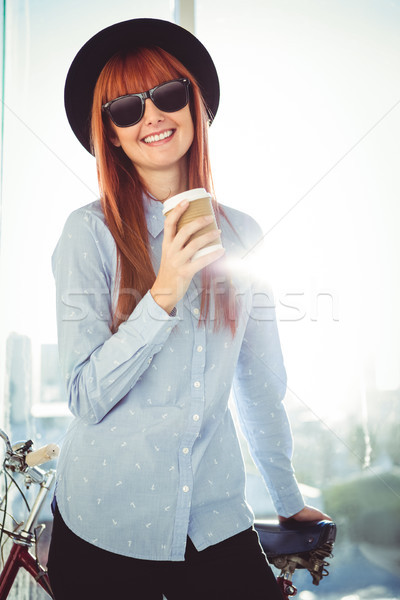 Smiling hipster woman leaning on a bike Stock photo © wavebreak_media