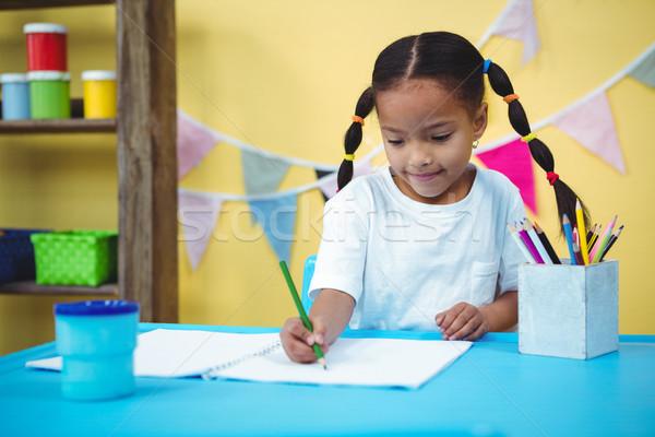 Smiling girl drawing in her colouring book Stock photo © wavebreak_media