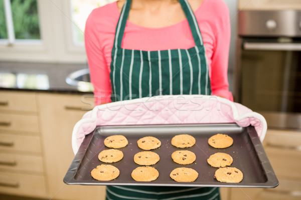 Mid section of woman showing biscuits on baking tin Stock photo © wavebreak_media
