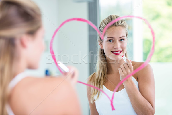Nő rúzs néz tükör fürdőszoba boldog Stock fotó © wavebreak_media