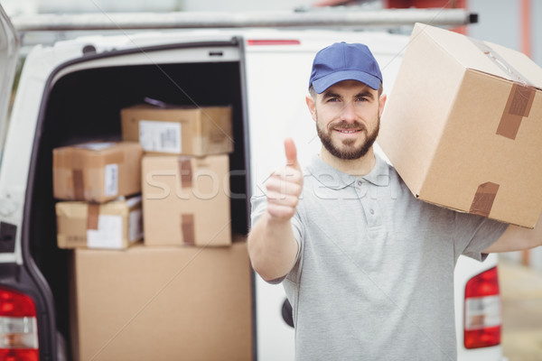 Delivery man holding package Stock photo © wavebreak_media