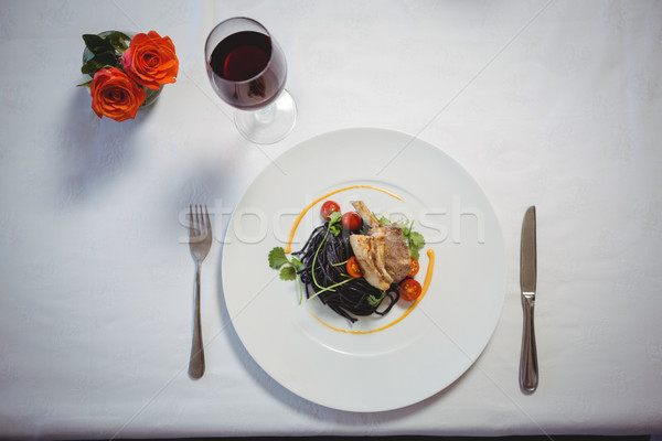 Squid ink spaghetti dish with basil with flowers and red wine Stock photo © wavebreak_media
