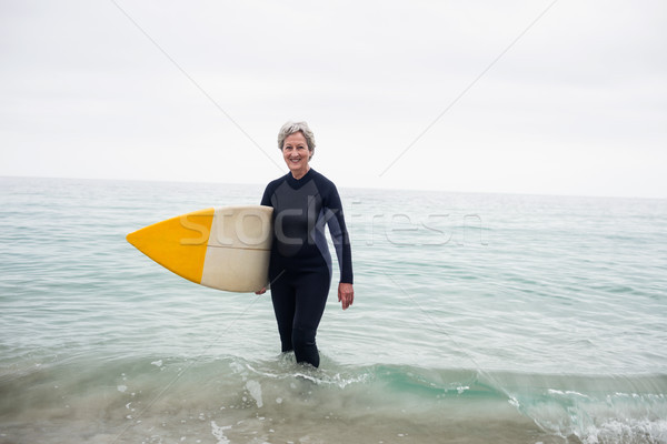 Senior woman in wetsuit standing in water with surfboard on the  Stock photo © wavebreak_media
