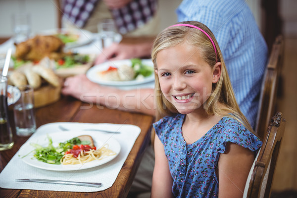 Smiling girl sitting at dining table  Stock photo © wavebreak_media