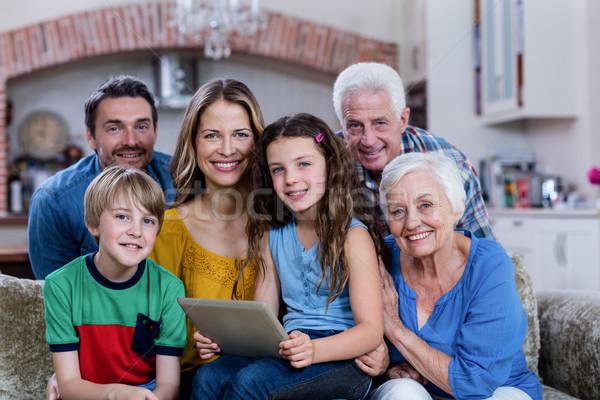 Portrait of multi-generation family sitting on sofa and using di Stock photo © wavebreak_media