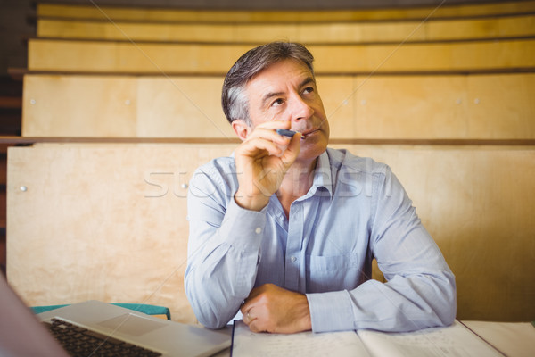 Thoughtful professor sitting at desk with book and laptop Stock photo © wavebreak_media