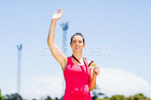 Female athlete waving her hand and showing gold medal Stock photo © wavebreak_media