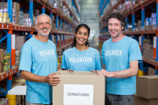 Heureux bénévoles souriant posant dons boîte Photo stock © wavebreak_media