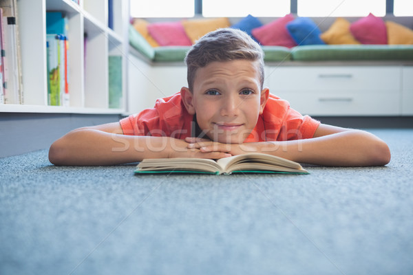 Schoolboy lying on floor and reading a book in library Stock photo © wavebreak_media