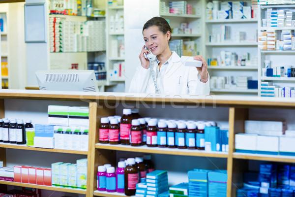 Pharmacist holding medicine box while talking on phone Stock photo © wavebreak_media