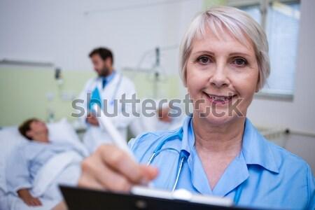 Ritratto sorridere infermiera iscritto appunti ospedale Foto d'archivio © wavebreak_media