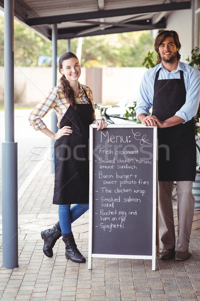Waiter and waitress standing with menu board outside the cafe Stock photo © wavebreak_media