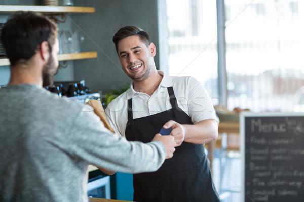 Waiter giving bread to customer at counter Stock photo © wavebreak_media