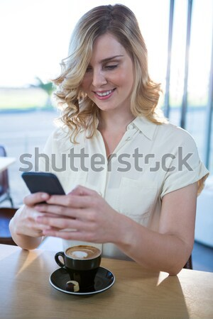 Woman using her mobile phone in the coffee shop Stock photo © wavebreak_media