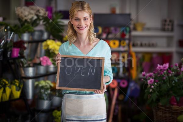 Smiling female florist holding open sign on slate in flower shop Stock photo © wavebreak_media