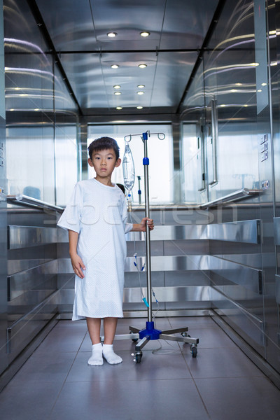 Smiling boy patient holding intravenous iv drip stand in lift Stock photo © wavebreak_media