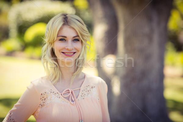Smiling woman standing in park Stock photo © wavebreak_media
