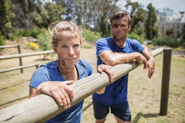 Tired man and woman leaning on a hurdle during obstacle course Stock photo © wavebreak_media