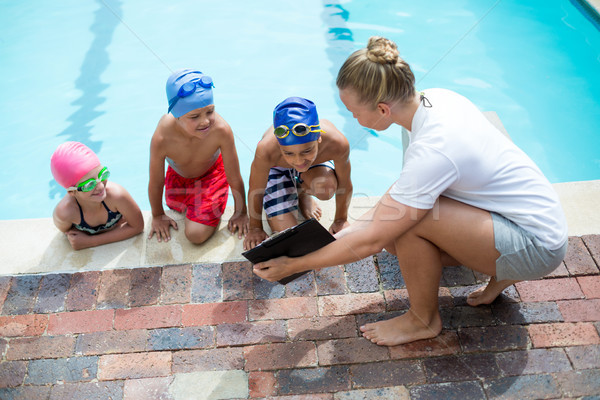 Female instructor showing clipboard to children at pool side Stock photo © wavebreak_media