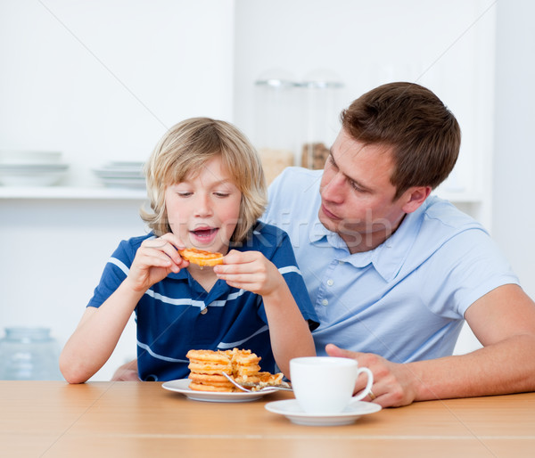 Charming father and his son eating waffles Stock photo © wavebreak_media