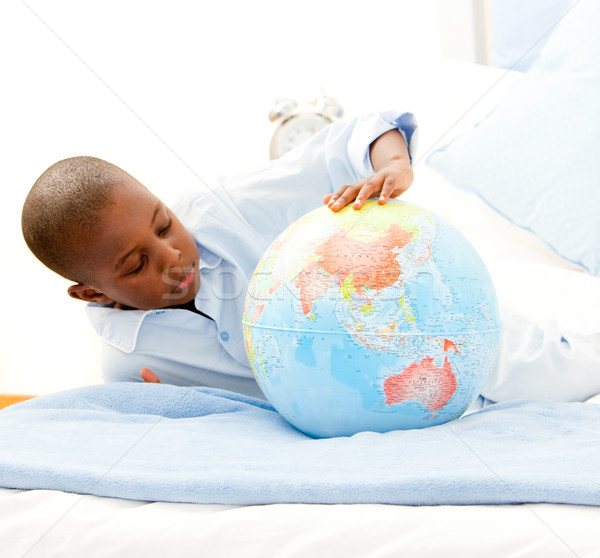 Cute little boy playing with a terrestrial globe Stock photo © wavebreak_media