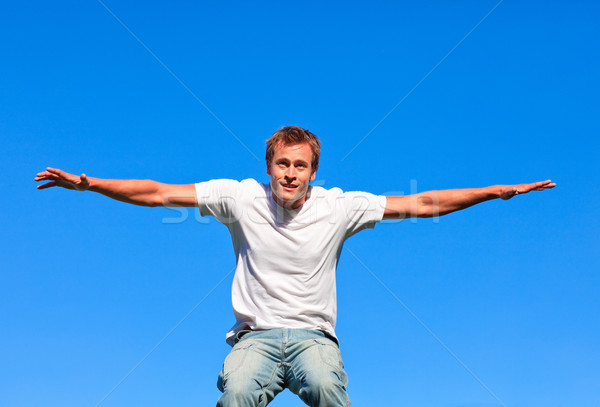 Portrait of a positive Man jumping in the air outdoor against a blue sky background Stock photo © wavebreak_media