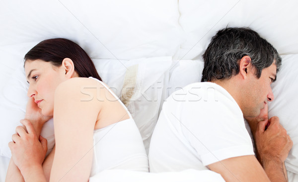 Upset couple sleeping in their bed separately after a row Stock photo © wavebreak_media