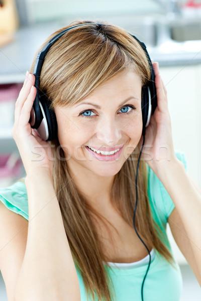 Heldere kaukasisch vrouw luisteren naar muziek hoofdtelefoon keuken Stockfoto © wavebreak_media