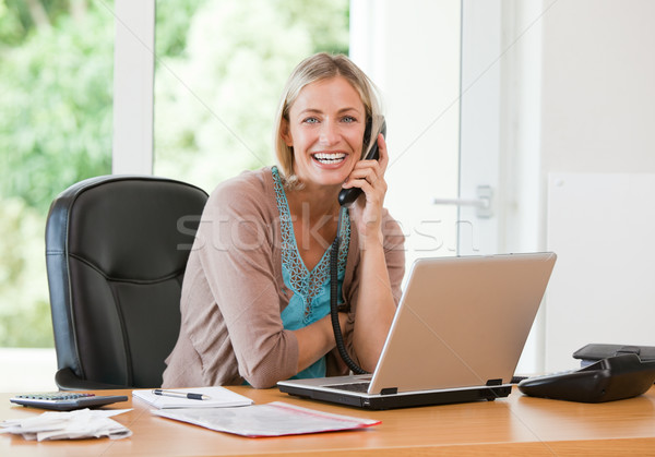 Woman working on her computer while she is phoning at home Stock photo © wavebreak_media