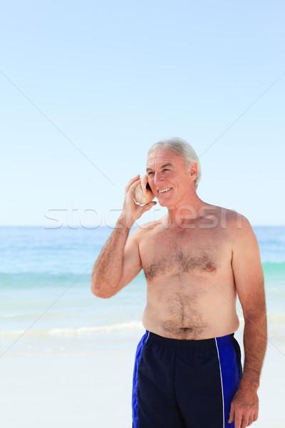 Senior homem escuta concha praia sorrir Foto stock © wavebreak_media