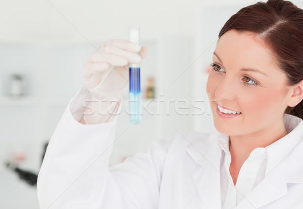 Sonriendo científico mirando tubo de ensayo laboratorio mujer Foto stock © wavebreak_media