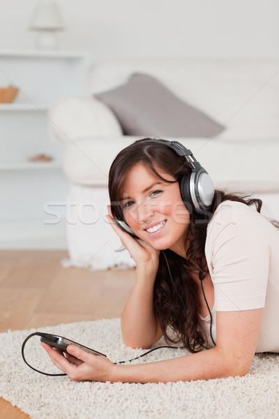 Stockfoto: Mooie · brunette · vrouwelijke · luisteren · naar · muziek · mp3-speler · tapijt