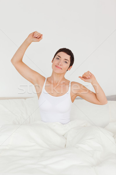 Portrait of a cute woman stretching her arms to wake up Stock photo © wavebreak_media