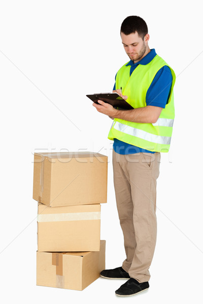 Side view of young delivery man filling in delivery note against a white background Stock photo © wavebreak_media