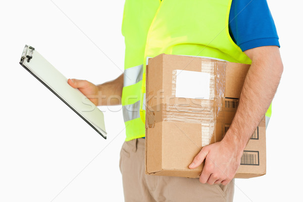 Side view of delivery man with delivery note and parcel against a white background Stock photo © wavebreak_media