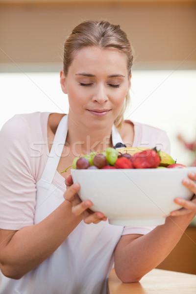 Portrait of a woman smelling a fruit basket in her kitchen Stock photo © wavebreak_media