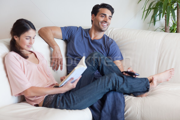 Woman reading a book while her husband is watching television in their living room Stock photo © wavebreak_media